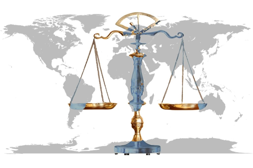 scales of justice with map of the world in background